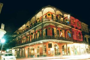 New Orleans, Louisiana, USA. Night time view of multi-story building with decorative iron galleries, Royal Street at St. Peter, French Quarter. Author: Falkue at de.wikipedia.