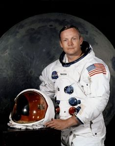 Portrait of Astronaut Neil A. Armstrong, commander of the Apollo 11 Lunar Landing mission in his space suit, with his helmet on the table in front of him. Behind him is a large photograph of the lunar surface. NASA.