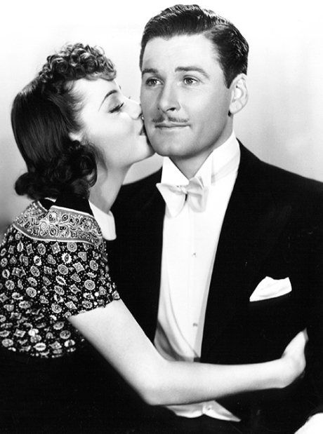Olivia de Havilland and Errol Flynn for a kiss that is more than a kiss, a message of love from the 1930's.